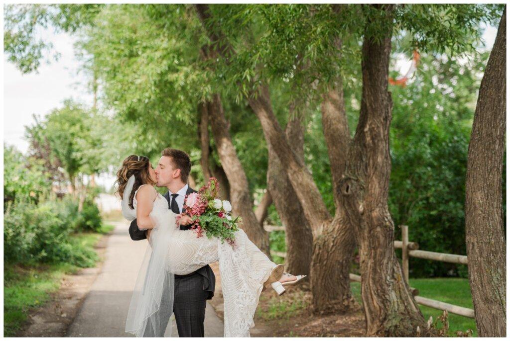 Taylor & Jolene - Emerald Park Wedding - 16 - Groom carries bride down tree lined path