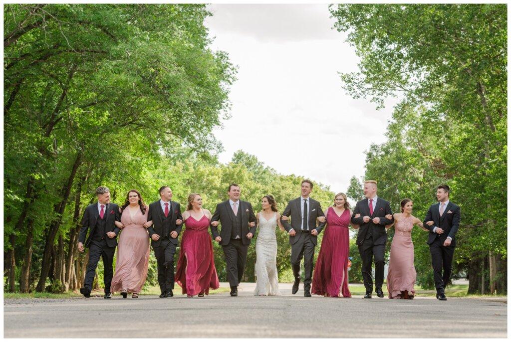 Taylor & Jolene - Emerald Park Wedding - 22 - Bridal party walks arm in arm down the road