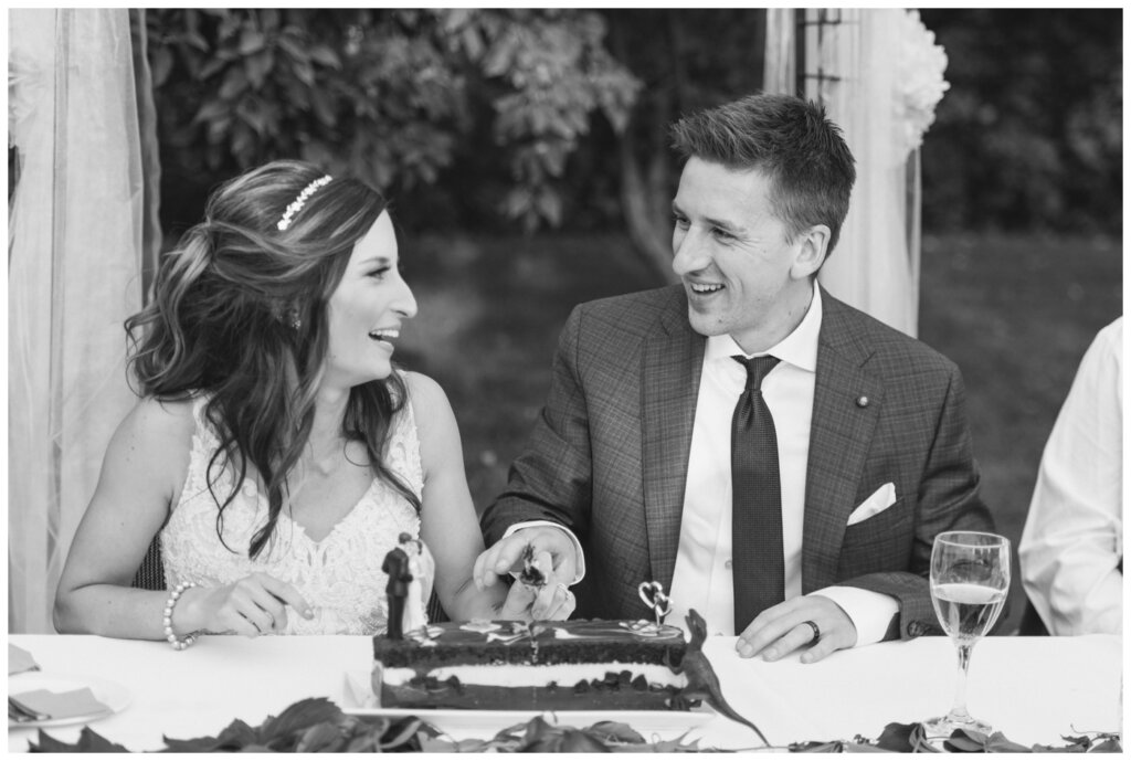Taylor & Jolene - White City Wedding - 37 - Bride & Groom cut their wedding cake adorned with cake topper and velociraptor