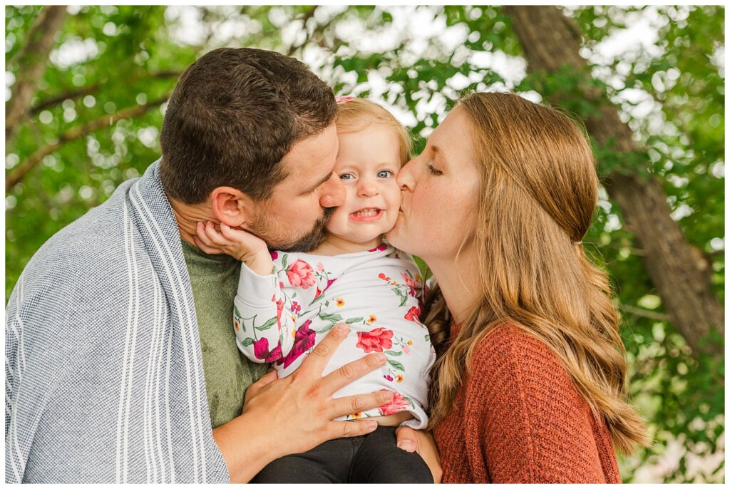 Eyre Family 2021 - AE Wilson Park - Family Photo Shoot - 09 - Mom and dad give daughter smooshy kisses