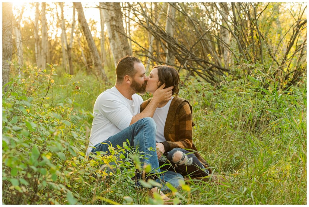 Kim & Lisa Korchinski - White Butte Trails - Family Photo Session 2021 - 07 - Husband and wife kiss, sitting on ground at white butte trails