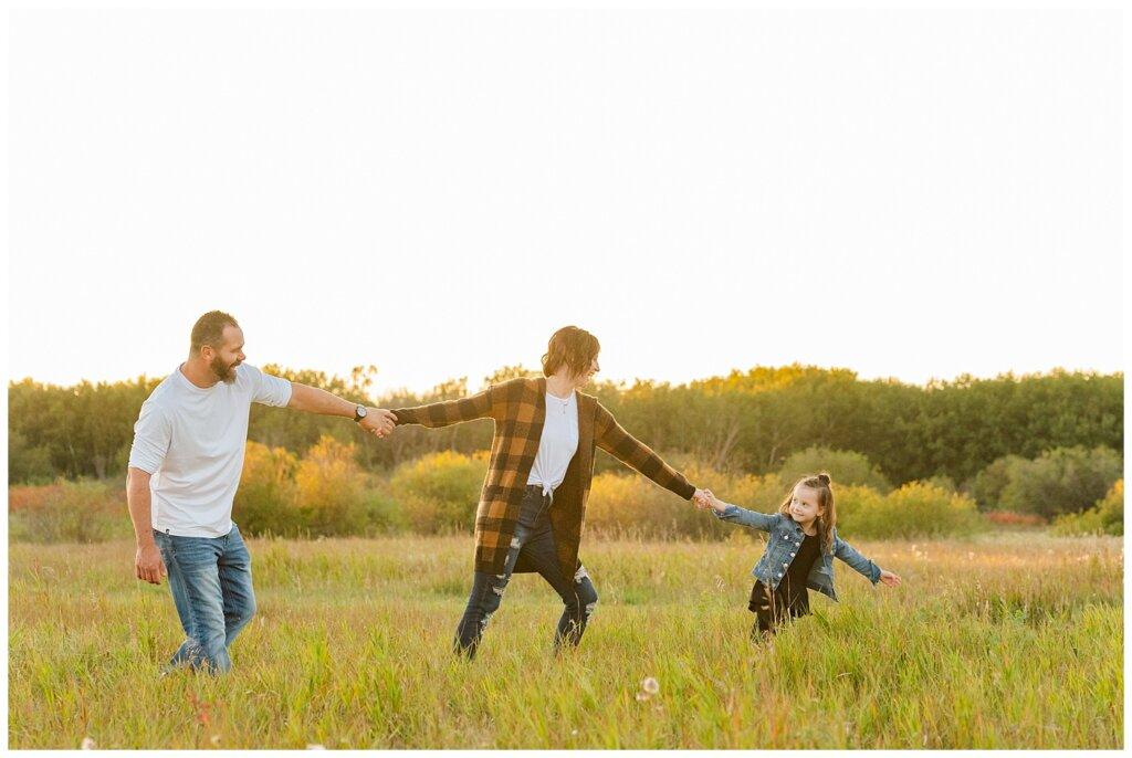 Kim & Lisa Korchinski - White Butte Trails - Family Photo Session 2021 - 12 - Daughter leading parents through field