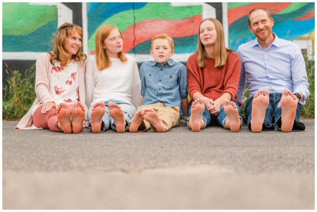 Schoenroth Family - Cathedral Village Regina - 16 - Family sit barefoot in the alley
