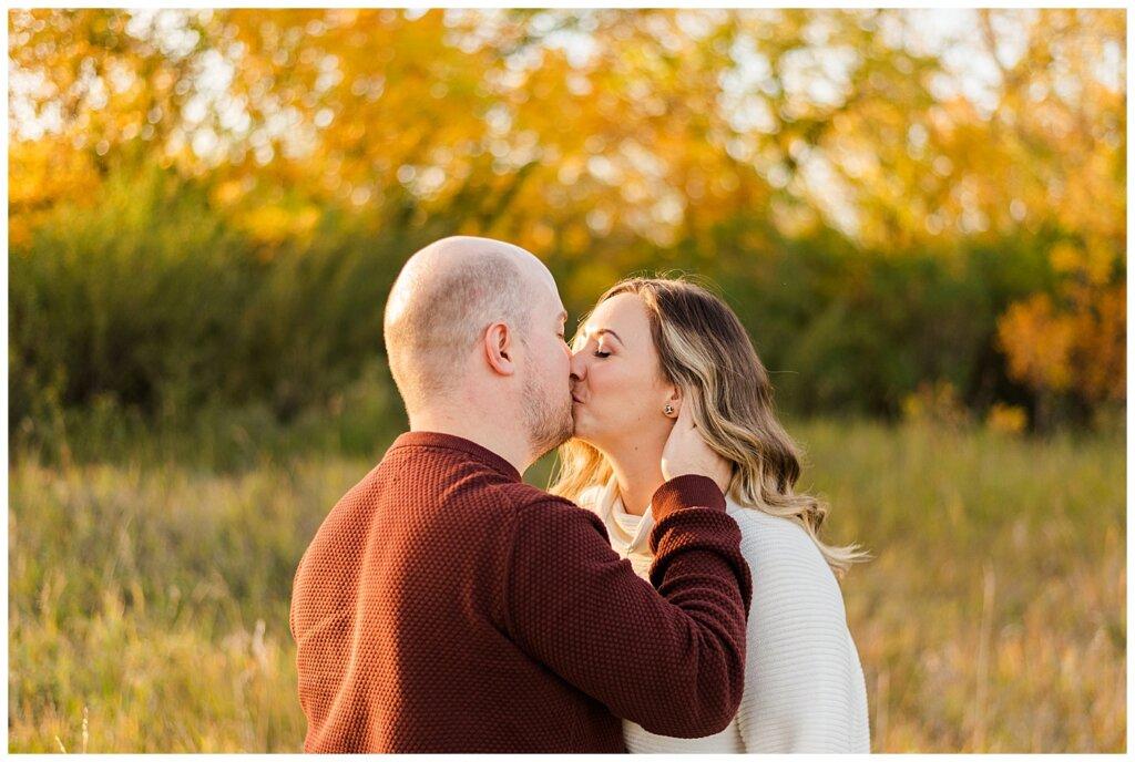 Trevor & Kim - Regina Engagement Session - Wascana Centre Habitat Conservation Area - 12 - Couple Kissing in field