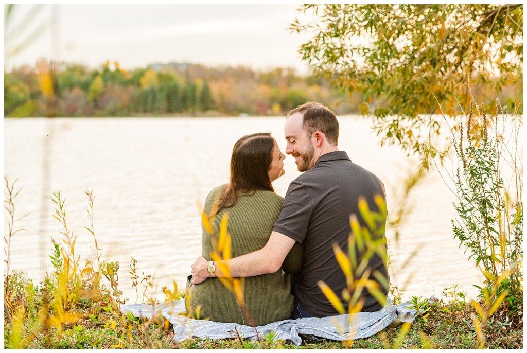 Andrew & Alisha - Engagement Session - 05 - Couple sitting on bank of Wascana Lake