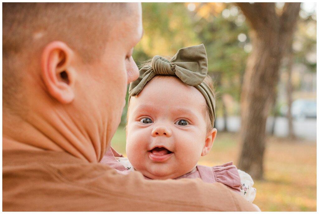 Filby Family - Regina Family Photography - Wascana Park - 05 - Isla smiling at camera over dad's shoulder