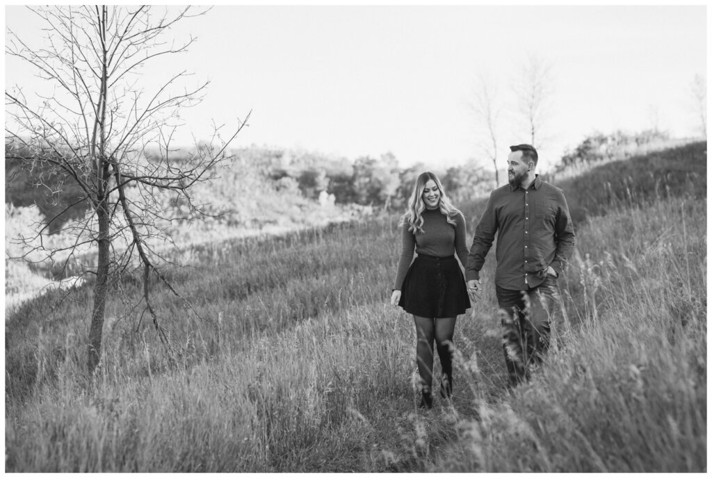 Jared & Jenna - Wascana Trails - 01 - Couple walking through field in black and white