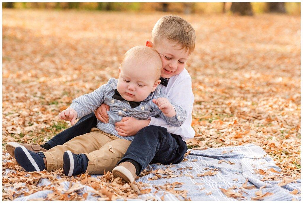 Nickel Family - Regina Science Centre - Family Photo Session - 04 - Older brother huggin infant on blanket