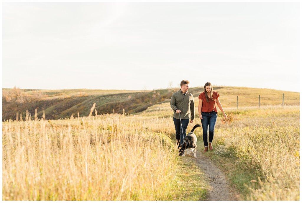 Tris & Jana - Engagement Session - Wascana Trails - 01 - Couple walking with Dog on trail