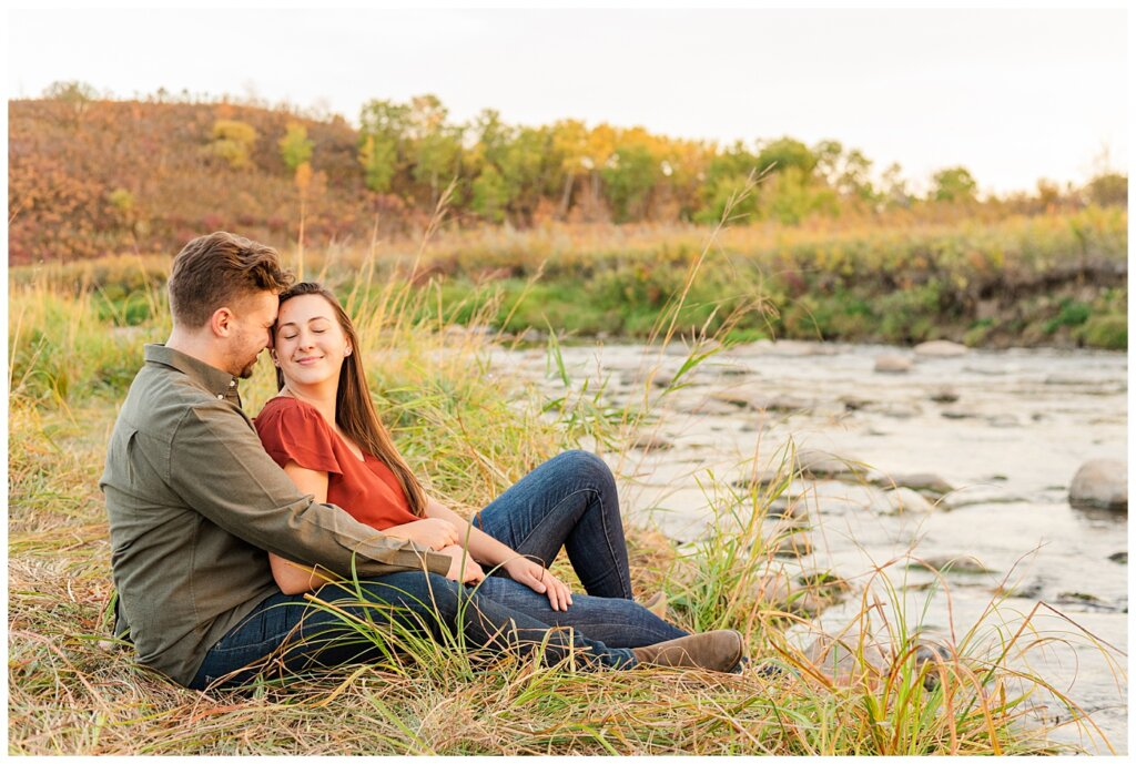 Tris & Jana - Engagement Session - Wascana Trails - 11 - Sitting by Wascana Creek