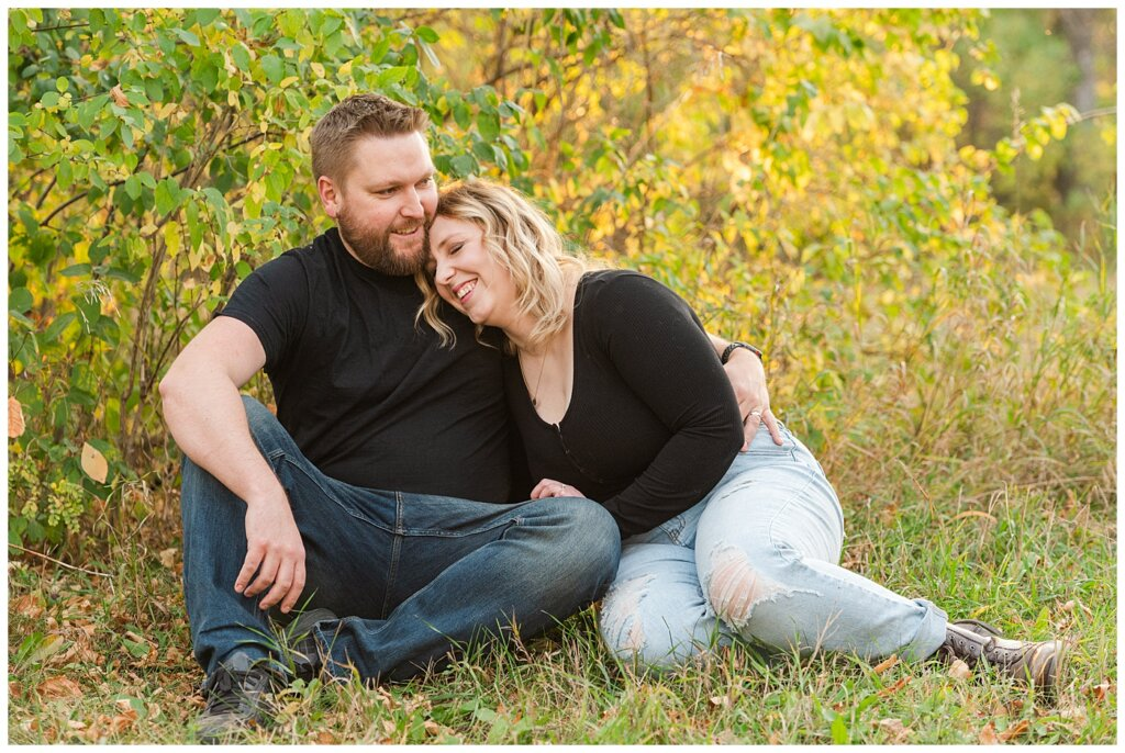 Tyrel & Allison - Regina Anniversary Session - Douglas Park Hill - 01 - Couple laughing as they sit on the grass