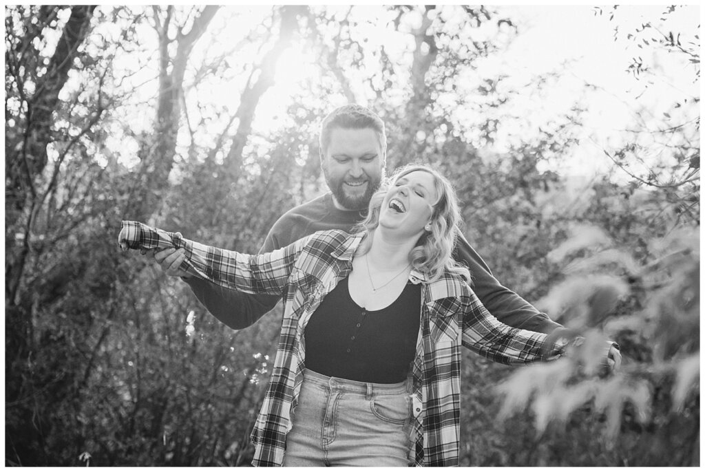 Tyrel & Allison - Regina Anniversary Session - Douglas Park Hill - 06 - Husband making wife laugh as he uses her arms like an airplane